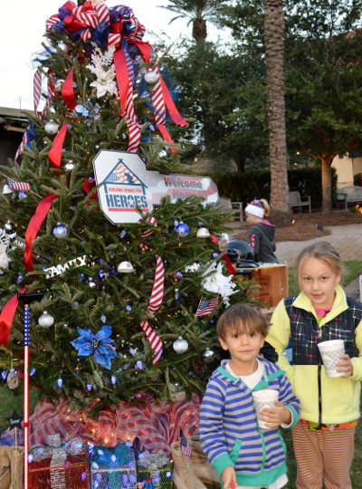 CROMWELL LETCHER (l) and Maggie Lee Letcher admire the Building Homes for Heroes tree at the Nov. 24 Festival of Trees kick-off. The youngsters are the grandchildren of Chip and Betty Letcher of Inlet Beach