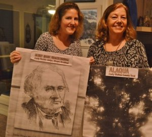 BRENDA REES (right) and daughter Lauren Rees display images of Henry Marie Brackenridge and live oak trees on his Alaqua property. The anniversary of Walton County's founding was celebrated on Dec. 29, as has been the tradition since 2004. Brenda Rees, initiator of the event, hosted the celebration at her Eastern Lake home. (Photo by Dotty Nist)