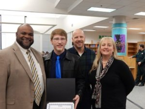 WALTON HIGH SCHOOL PRINCIPAL Russell Hughes shares in the celebration of Evan Cowie's latest academic achievement along with his parents, George and Terri Cowie. Evan was named Walton County's Sunshine State Scholar.