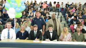 WALTON SENIORS Koleman Truett (left middle) and Danny Hicks (right middle) inked football scholarship offers on Thursday at Walton High School. Truett is off to Ave Maria University while Hicks will attend Huntingdon College. (Photo by Patrick Casey)