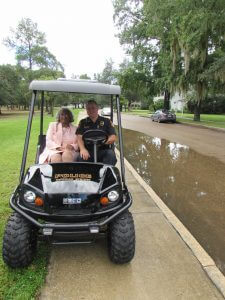 """THE SUN BROKE THROUGH just long enough for DeFuniak Springs City Marshal Mark Weeks to escort Ms. Wilkerson down Circle Drive to her """"Woman of Light"""" commemorative stone. Wilkerson was honored Aug. 12.  (Photo by Elizabeth Sinclair)"""